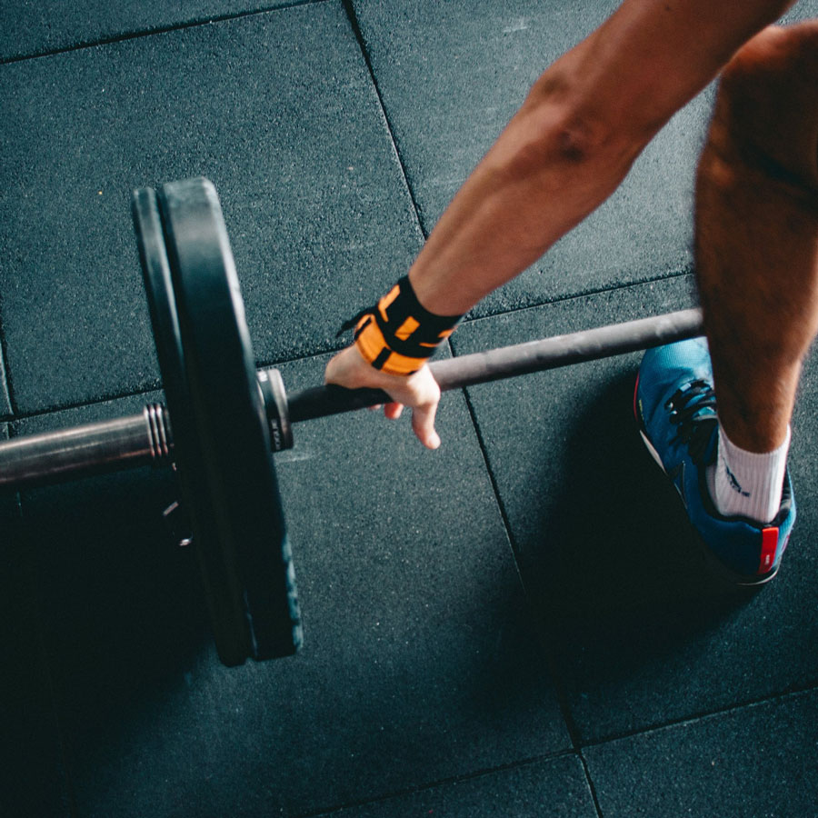 a close up shot of a man grabbing a barbell on a gym floor