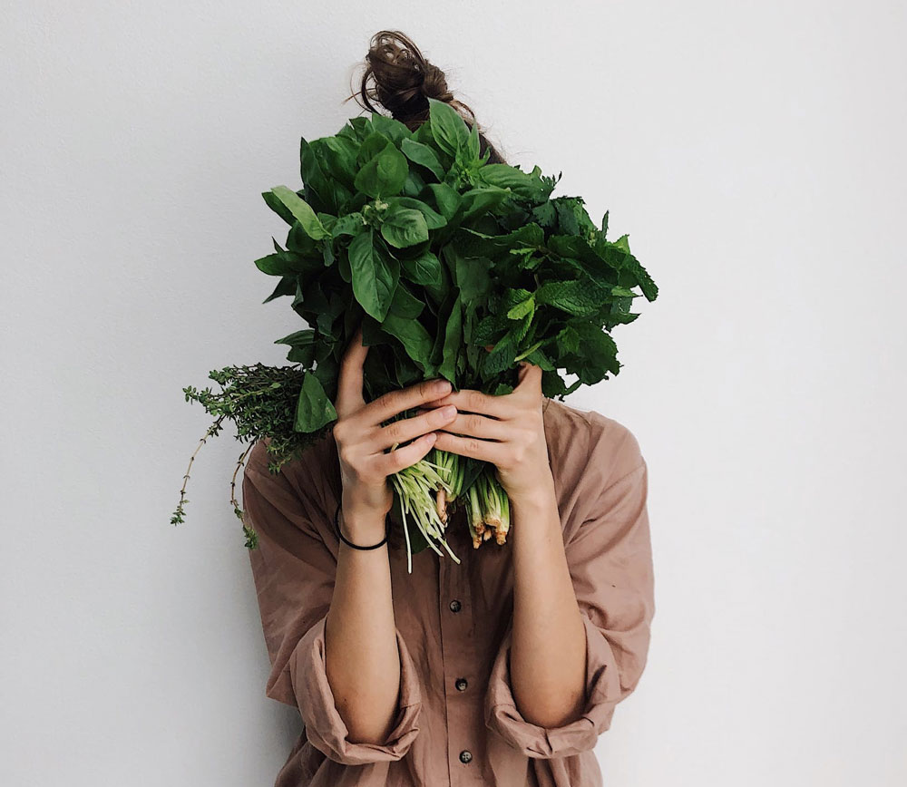 a woman in an earthy shirt holding leafy green vegetables in front of her face