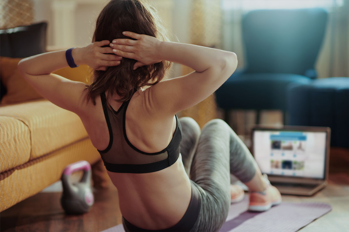 a young woman doing situps in her living room